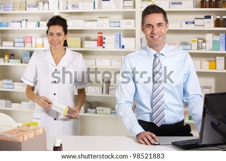 UK nurse and pharmacist working in pharmacy - stock photo
