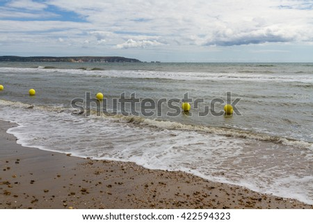 UK pebble beach with line of yellow buoys.  Isle of Wight Needles in background. - stock photo