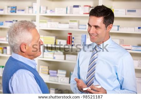 UK pharmacist serving  senior man in pharmacy - stock photo