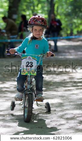 UKRAINE, KIEV - SEPTEMBER 11: Young biker Zayceva Katya, at the child amateur bicycle competition We are the champions, on September 11, 2010 at Ukraine, Kiev. - stock photo