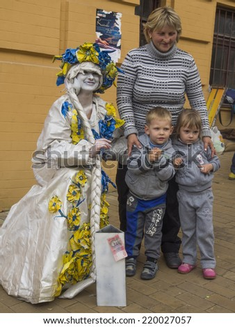 """UKRAINE, KYIV - September 27, 2014: Woman with two children photographed with a """"live"""" sculpture, Andrew's Descent, Kiev, Ukraine - stock photo"""