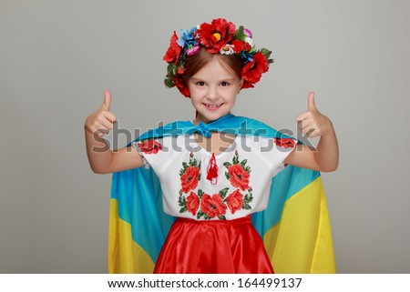 Ukrainian Beautiful little girl with a sweet smile, holding a big flag of Ukraine and is a fan of football competition, olympics, sports championships - stock photo