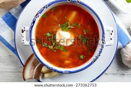 Ukrainian beetroot soup - borscht, on blue napkin, on wooden background - stock photo