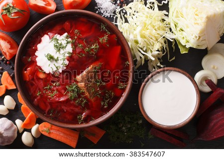 Ukrainian food: red soup borsch with ingredients on slate board closeup. Horizontal view from above