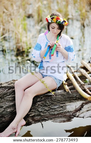Ukrainian girl in a dress and a wreath of flowers on her head sitting on a log by the river - stock photo