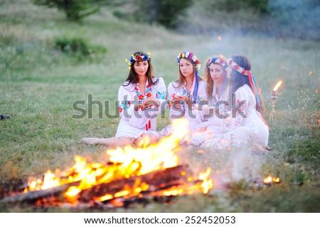 Ukrainian girl in shirts sitting around the campfire - stock photo