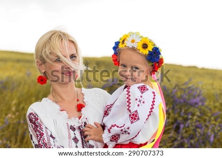 Ukrainian mother and her little daughter in national costumes - stock photo
