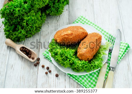 Ukrainian national dish , chicken Kiev  , cutlets of chicken meat in breadcrumbs with butter , dill, pepper and lettuce on a wooden background - stock photo