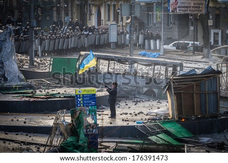 Ukrainian revolutionary waving flag of Ukraine. Ukraine, Kiev, street Hrushevskoho (01/20/2014) - stock photo