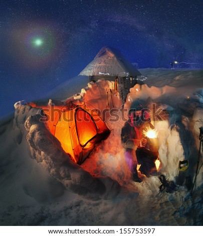 Ukrainian tourists celebrate New Year in extreme conditions on the glacier, the highest peak in the country- Goverla, Montenegrin ridge, 2061 meters, building a protective snow wall tent.  - stock photo