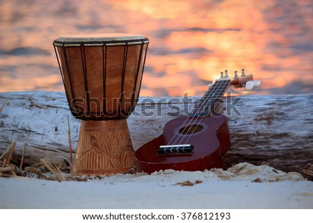 Ukulele and ethnic drum over a sunset beach. - stock photo