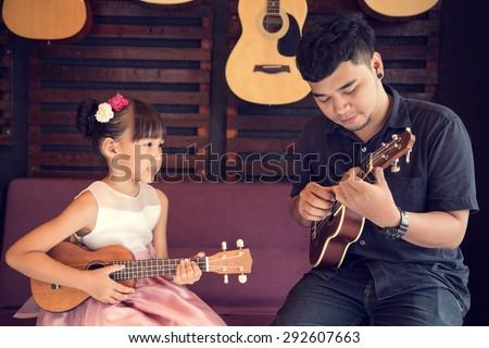 Ukulele Guitar teacher teach music in school - stock photo