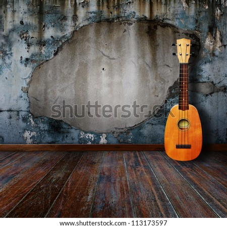 Ukulele in grunge room. - stock photo