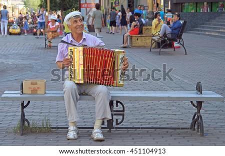 ULAN UDE, RUSSIA - JULY 17, 2015: man is playing bayan outdoor in Ulan Ude, Russia - stock photo