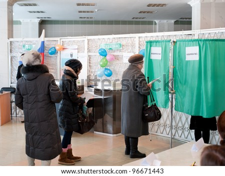 ULAN-UDE, RUSSIA - MARCH 4: Unidentified voters at the local polling station 699 stand in line to voting booths at the presidential election of Russian Federation on March 4, 2012 in Ulan-Ude, Buryatia, Russia. - stock photo
