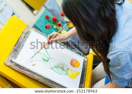 ULAN-UDE, RUSSIA - MAY 10, 2011: An unidentified girl paints at a drawing school of the City Palace of Childrens and Junior Arts, the biggest centre offering hobby circles and studies for children. - stock photo