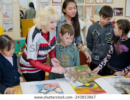 "ULAN-UDE, RUSSIA - MAY 10, 2011: Tatiana Shapovalova, the leader of the drawing school ""Look"", teaches children in the City Palace of Childrens and Junior Arts, offering hobby circles for kids. - stock photo"