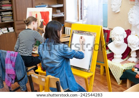 ULAN-UDE, RUSSIA - MAY 10, 2011: Two unidentified girls paint at a drawing school of the City Palace of Childrens and Junior Arts, the biggest centre offering hobby circles and studies for children. - stock photo