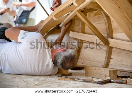 ULM (GERMANY) - 06 JULY 2014 - Boat builder at International Danube festival in Ulm, Germany working on the wooden frame of a boat watched by a group of spectators - stock photo