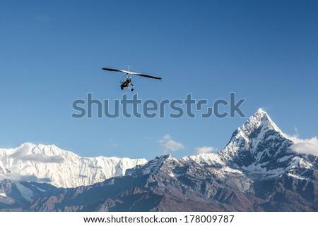 Ultra light plane flying over the Annapurna mountain range in the Himalayas near Pokhara, Nepal. The summit on the right is the Machapuchare (6993m), aka the fishtail mountain. - stock photo