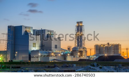 Ultra modern coal powered electrical power plant during sunset under a blue and orange sky - stock photo