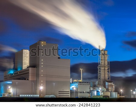 Ultra modern coal powered electrical power plant with smoking chimney during sunset under a blue sky - stock photo
