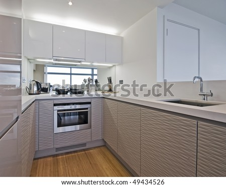ultra modern kitchen counter with white stone worktop and appliances - stock photo