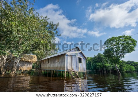 Ultra wide angle view of wooden house built in Amazon rainforest over black river, Brazil - stock photo