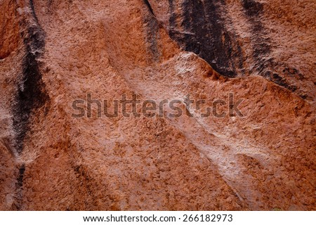 Uluru - Ayers Rock. Aboriginal sacred place. UNESO world heritage. Red sandstone rock closeup with day changing color painting. PR available - image approved for commercial use by Park authorities. - stock photo