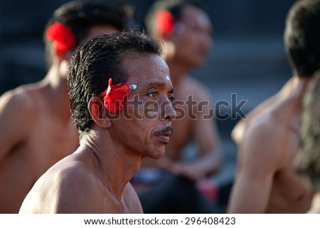 ULUWATU, BALI - CIRCA January 2011 - A Balinese man during a traditional Fire Dance ceremony at the Uluwatu Temple. The ancient Hindu temple features ocean cliff views and traditional dance shows. - stock photo