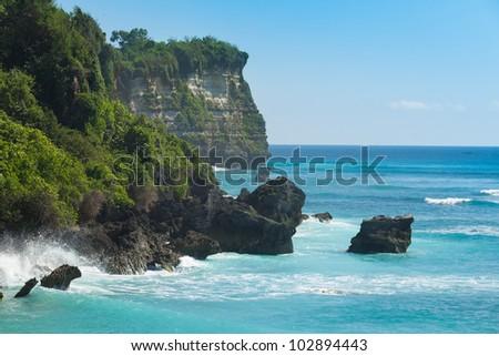 UluWatu coastline with beaautiful rocky cliffs and turquoise wavey sea. - stock photo