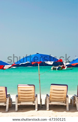 Umbrella and chair on the beach - stock photo