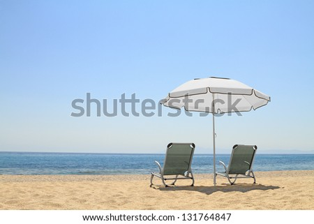 Umbrella and lounge chairs on idyllic beach, in Thassos island - Greece - stock photo