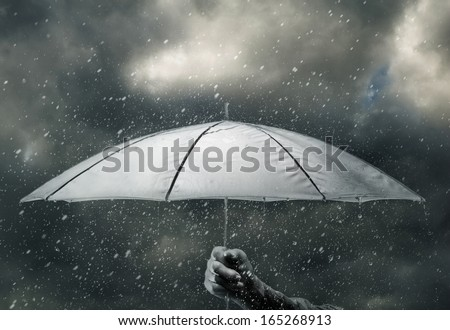 Umbrella in hand under raindrops of thunderstorm - stock photo