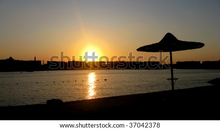 Umbrella on beach during sunset, in Marina, Egypt. - stock photo