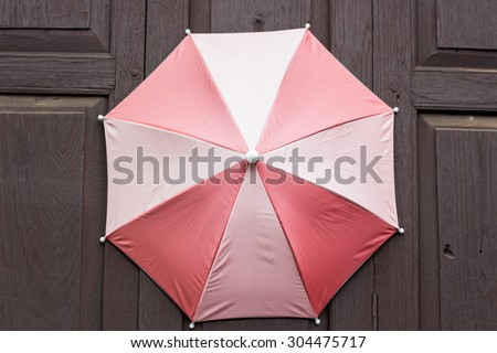 umbrella on wood wall - stock photo