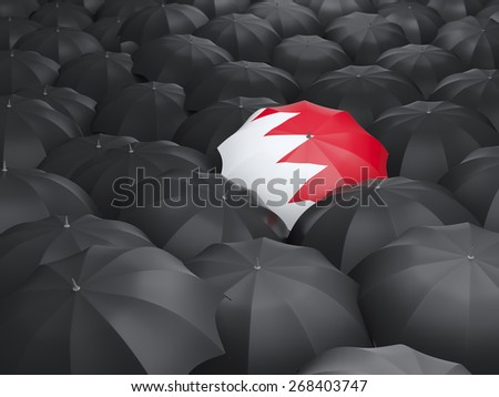 Umbrella with flag of bahrain over black umbrellas - stock photo