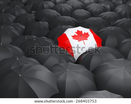 Umbrella with flag of canada over black umbrellas - stock photo