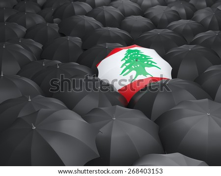 Umbrella with flag of lebanon over black umbrellas - stock photo