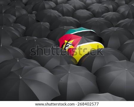 Umbrella with flag of mozambique over black umbrellas - stock photo