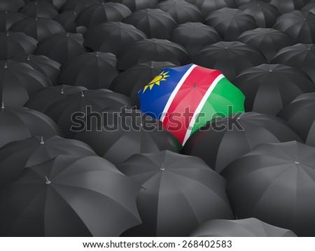 Umbrella with flag of namibia over black umbrellas - stock photo