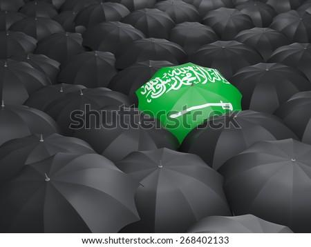 Umbrella with flag of saudi arabia over black umbrellas - stock photo