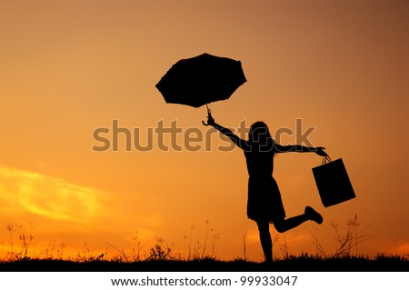 Umbrella Woman holding shopping bags  in sunset silhouette - stock photo