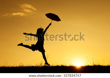 Umbrella woman jumping and sunset silhouette with copy space. - stock photo