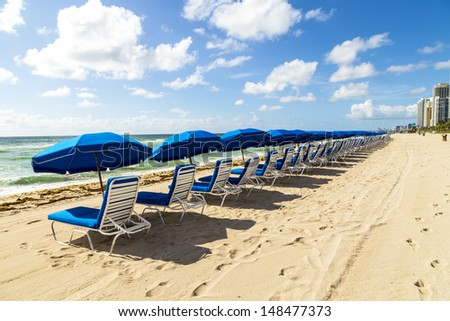 umbrellas and empty beach couches at the beach in Miami - stock photo