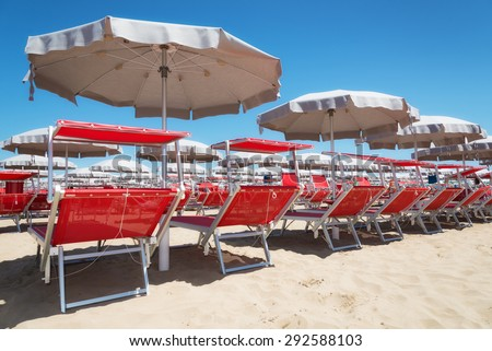 Umbrellas and sunbeds in Rimini and Riccione and Cattolica Beach, Italy - stock photo