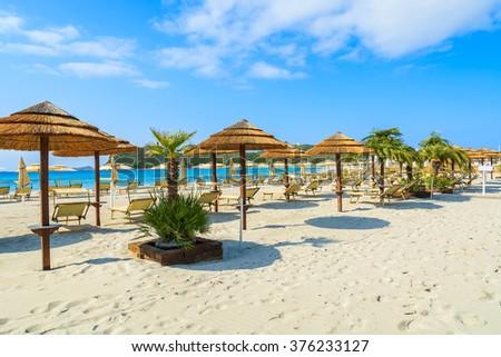Umbrellas and sunbeds on sandy Villasimius beach, Sardinia island, Italy - stock photo