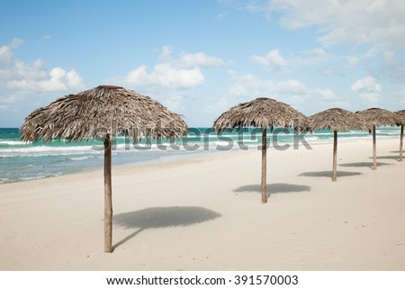 Umbrellas from royal palm leaves, parasole on sandy beach in Varadero on Cuba with turquoise Caribbean sea. - stock photo