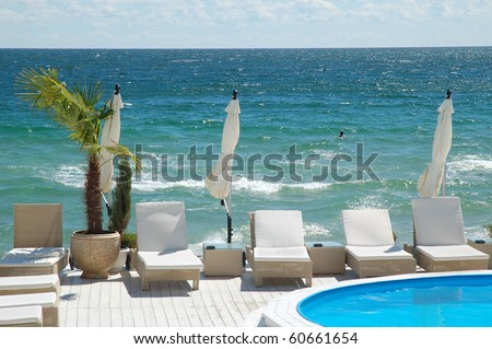 Umbrellas, swimming pool and loungers on the luxury beach-club - stock photo