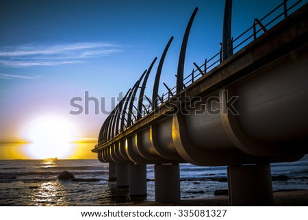 Umhlanga Pier in durban on a clear morning in the sunrise over the Indian ocean - stock photo
